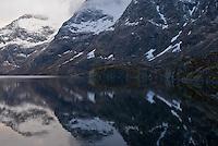 reflection of snow covered peaks in lake, Å, Norway