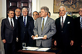 United States President Bill Clinton makes a statement as he signs the a bill extending $5.7 billion of cash benefits for the unemployed in the Roosevelt Room of the White House in Washington, DC on Thursday, March 4, 1993.  The emergency bill passed Congress earlier in the day.  Pictured in the front row behind the President: US Senator Donald W. Riegle, Jr. (Democrat of Michigan), US Senator Daniel Patrick Moynihan (Democrat of New York), US Senate Majority Leader George J. Mitchell (Democrat of Maine) and Speaker of the US House of Representatives Tom Foley (Democrat of Washington). <br /> Credit: Jim Colburn / Pool via CNP