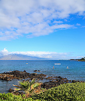 Standup paddleboarders, kayakers and outrigger canoe paddlers tour around the waters off Wailea Beach, South Maui.