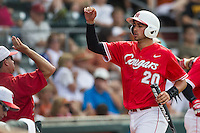 Houston Cougars designated hitter Justin Montemayor (20) is greeted by his dugout after scoring during the NCAA baseball game against the Texas Longhorns on June 6, 2014 at UFCU Disch–Falk Field in Austin, Texas. The Longhorns defeated the Cougars 4-2 in Game 1 of the NCAA Super Regional. (Andrew Woolley/Four Seam Images)