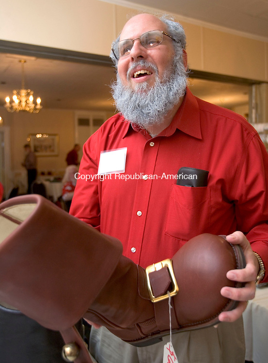 TORRINGTON, CT. 08 October 2011-100811SV05--Frank Cardello of Torrington checks out a new pair of Santa boots during The Connecticut Society of Santa&rsquo;s convention at the Yankee Pedlar Inn in Torrington Saturday. The society returned to Torrington, home of the Carl Bozenski's Christmas Village, for the second year for its annual convention. The Santas strive for authenticity down to their white beards.<br /> Steven Valenti Republican-American