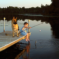 Young boy and his dog fishing from the lake dock.