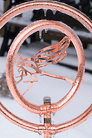 Ice hanging from ornamental copper water irrigation sprayer, with dragonfly decoration in winter snow