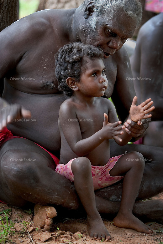 Child sits in his grandfather's lap during a cleansing ceremony on Tiwi Islands.  <br /> A cleansing ceremony is the final ceremony in the death of a family member.  A year or so after the funeral the family gets together and paints pukamani poles and places them around the grave.  Some communities won't say the name of the deceased or go back into the home until there is a big cleansing rain.  But rituals vary from community to community.