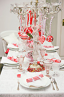 A crystal candelabra in the centre of the dining table has been decorated with red and white hearts and Christmas baubles