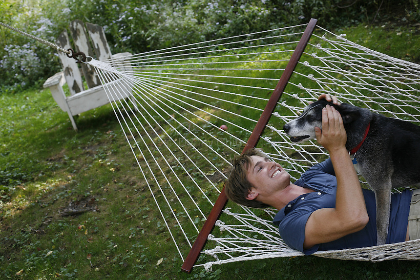Will Tobin in a hammock with a dog