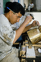 Tunis, Tunisia.  Brass Worker Hammering a Design into a Pot.