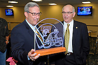 12 August 2011:  FIU Biscayne Bay Campus Vice Provost Steve Moll (left) shows an illuminated etching of an FIU football helmet to FIU Alumni Association Director Bill Draughon (right) during the FIU 2011 Panther Preview at University Park Stadium in Miami, Florida.