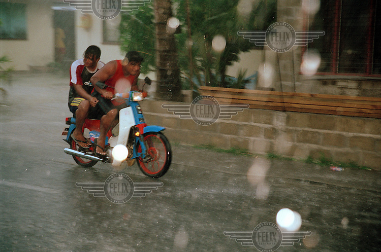 Two young men drive through the heavy rain on a motorbike during a storm...
