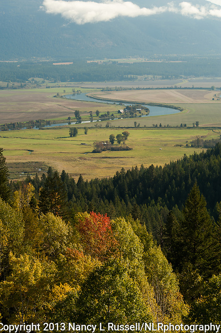 Fall colors in the Kootenai valley with the Kootenai river flowing through the valley and the Selkirk mountains in the background
