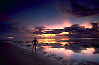 A man standing on the beach at Naviaquia Point on Venua Island watching a purple and orange sunset. Venua Island is part of the Fiji Islands in the South Pacific.