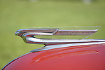 Westbury, New York, USA. June 12, 2016.  Flying Lady hood ornament with clear plastic insert in wings on 1940 red Chevrolet Super Deluxe sedan is on view at the Antique and Collectible Auto Show at the 50th Annual Spring Meet at Old Westbury Gardens, in the Gold Coast of Long Island, and sponsored by Greater New York Region, GNYR, Antique Automobile Club of America, AACA. Participating vehicles in the judged show included hundreds of domestic and foreign, antique, classic, collectible, and modern cars.