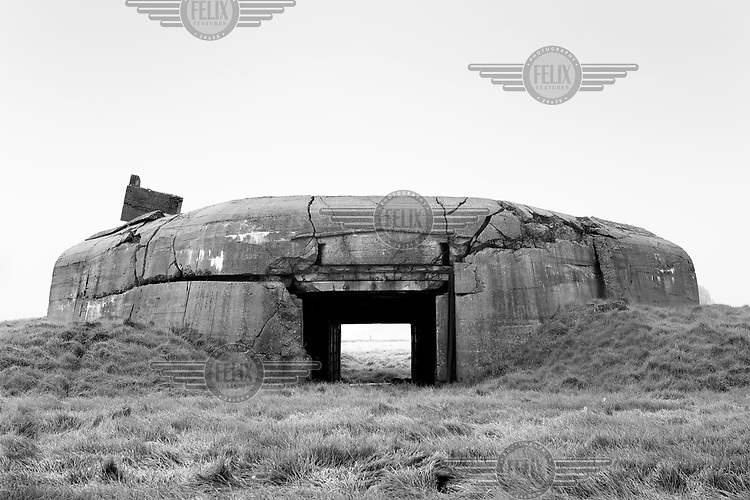 A former bunker stands abandoned along the route of the Atlantic Wall (Atlantikwall in German).The Atlantic Wall (or Atlantikwall in German) was a system of defensive structures built by Nazi Germany between 1942 and 1945, stretching over 1,670 miles (2,690 km) along the coast from the North of Norway to the border between France and Spain at the Pyrenees. The wall was intended to repulse an Allied attack on Nazi-occupied Europe and the largest concentration of structures was along the French coast since an invasion from Great Britain was assumed to be most likely. Slave labour and locals paid a minimum wage were drafted in to supply much of the labour. There are still thousands of ruined structures along the Atlantic coast in all countries where the wall stood except for Germany, where the bunkers were completely dismantled.
