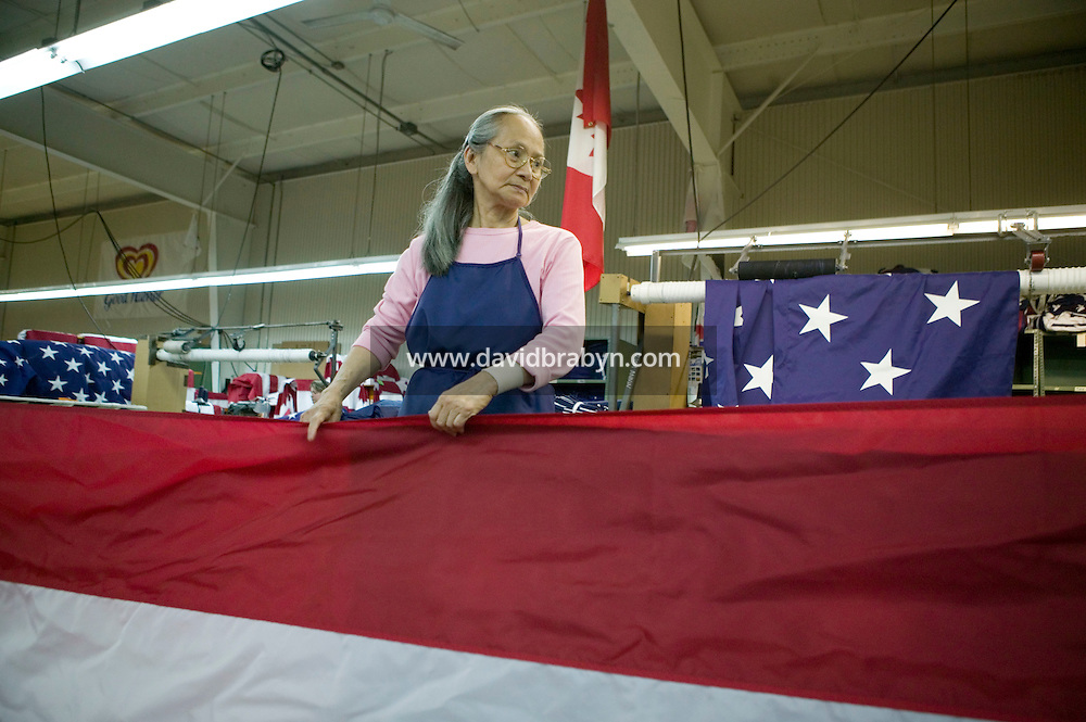 21 June 2005 - Oaks, PA - Leonor Ebba helps fold a completed American flag at the Annin & Co. flag manufacturing plant in Oaks, PA.