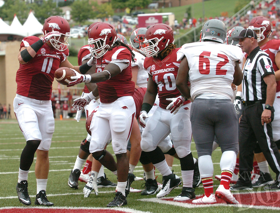 NWA Media/ANDY SHUPE - Arkansas running back Alex Collins, center, hands the ball to tight end A.J. Derby after scoring a touchdown against Nicholls during the first quarter Saturday, Sept. 6, 2014, at Razorback Stadium in Fayetteville