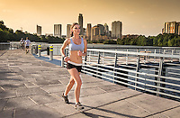 Female marathon runner trains on the the Boardwalk Trail along Lady Bird Lake in downtown Austin, Texas inset the Austin Cityscape at sunset.
