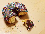 Partially eaten chocolate glazed doughnut with sprinkles on grease-stained paper.
