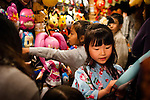 A young japanese girl picks her mask for the matsuri (festival). Cotton kimono (yukata) and masks are common during those traditional celebrations.