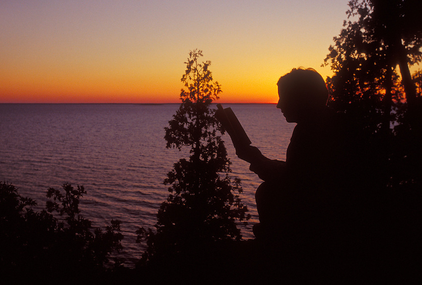 A WOMAN READS WHILE ENJOYING THE SUNSET OVER LAKE MICHIGAN FROM A BLUFF OVERLOOKING FAYETTE STATE HISTORICAL PARK ON THE GARDEN PENINSULA.