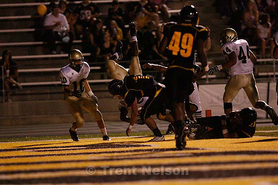 Skyline's Andy Rounds flips into the end zone for the touchdown over Cottonwood's Kyle Aberton. Cottonwood vs. Skyline High School football Friday, September 25 2009 in Salt Lake City.