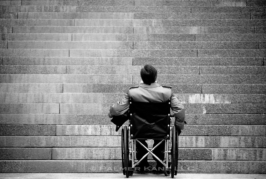 Handicapped man in wheelchair confronts physical impediment