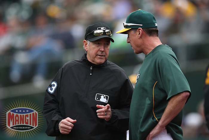 OAKLAND, CA - APRIL 2:  Umpire Mike Winters discusses a replay ruling with manager Bob Melvin #6 of the Oakland Athletics during the game against the Cleveland Indians at O.co Coliseum on Wednesday, April 2, 2014 in Oakland, California. Photo by Brad Mangin
