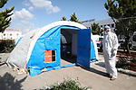 A photo taken on April 9, 2020, shows Syrian doctors  put on a protective suits examine sample from a patient at the Mobile test center for suspected coronavirus outside the National Hospital in the northern Syrian city of Azaz. Photo by Nayef ALaboud