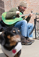 NWA Democrat-Gazette/CHARLIE KAIJO Mark Prime of Rogers strums his guitar with his dog Kiwi, Monday, March 26, 2018 in Downtown Rogers in Rogers . <br />