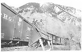 In the train view of D&amp;RG reefer car #121 derailed, leaing, and propped up with boards.  3 workmen are shown on the car.<br /> RGS  above Telluride, CO  Taken by Virden, Walter - 1909