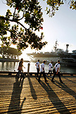 USA, California, San Diego, a group of individuals walk along the San Diego Bay towards the USS Midway Museum