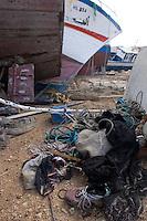 Cimitero delle barche...I barconi che trasportano i profughi vengono depositati in tre punti dell isola in attesa di essere smaltiti. ..Scarpe e indumenti sparsi vicino alle barche depositate nei pressi del porto...Lampedusa 05 Marzo 2011...Photo Serena Cremaschi Insidefoto..........