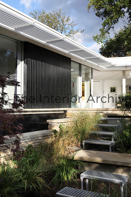 A garden planted with grasses whilst metal and wood steps lead up to a paved terrace area outside a modern house.
