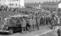 The funeral of murdered Citybus inspector, Alexander Millar, described as a captain in the UDA, Ulster Defence Association, departs from his home in North Belfast, N Ireland, UK. The hearse is flanked by para-military uniformed members of that organisation. Mr Millar was shot dead in his office At Ardoyne Bus Station after he was singled out by a gunman and an associate on 2nd May 1975. Although a UDA member would have been an obvious target for the Provisional IRA no claim or counter-claim was made to this effect. 197505020295b<br />