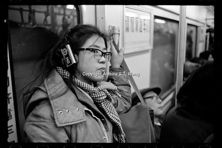 A Chinese woman listens to her headphone radio as she travels on an underground train in Beijing, China, 1985.