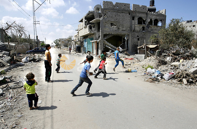 """Palestinian children play near a destroyed house in Khan Yunis in the southern Gaza Strip on September 11, 2014. Israel's deputy foreign minister,Tzahi Hanegbi , warned that Hamas was likely to resume """"violence"""" if it feels it has made no political gains from upcoming talks in Cairo. Photo by Abed Rahim Khatib"""