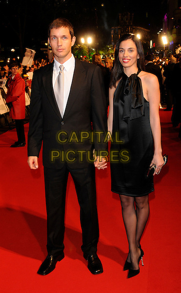 "MATTHEW MARSDEN & GUEST.The UK gala premiere of ""Rambo"", Vue Cinema, Leicester Square, London, England. .February 12th, 2008.full length black suit dress holding hands.CAP/DH.©David Hitchens/Capital Pictures."