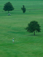 A man practices his golf swing on the grassy plain beneath an earthen dam in central Ohio.<br />