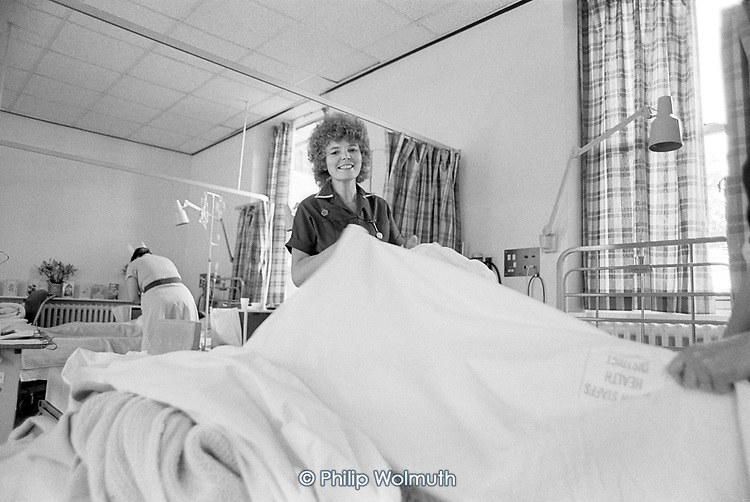 Nurse changing bed linen on a ward at City General Hospital, Stoke-on-Trent.