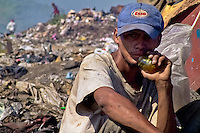 A Nicaraguan boy, a garbage recollector, sniffs glue in the garbage dump La Chureca, Managua, Nicaragua, 9 November 2004. La Chureca is the biggest garbage dump in Central America. Hundreds of trash recollectors search in tons of smouldering garbage mainly metals (copper, aluminium), others concentrate on glass which is cheap, but in bigger amount. The majority of the recyclers are families with children for whom recycling is a regular job. The children very often eat the food they find on the dump, none of them goes to school, they suffer from skin diseases, they have high levels of lead and DDT in blood.