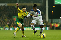 1st January 2020; Carrow Road, Norwich, Norfolk, England, English Premier League Football, Norwich versus Crystal Palace; Wilfried Zaha of Crystal Palace competes for the ball with Emi Buendia of Norwich City - Strictly Editorial Use Only. No use with unauthorized audio, video, data, fixture lists, club/league logos or 'live' services. Online in-match use limited to 120 images, no video emulation. No use in betting, games or single club/league/player publications