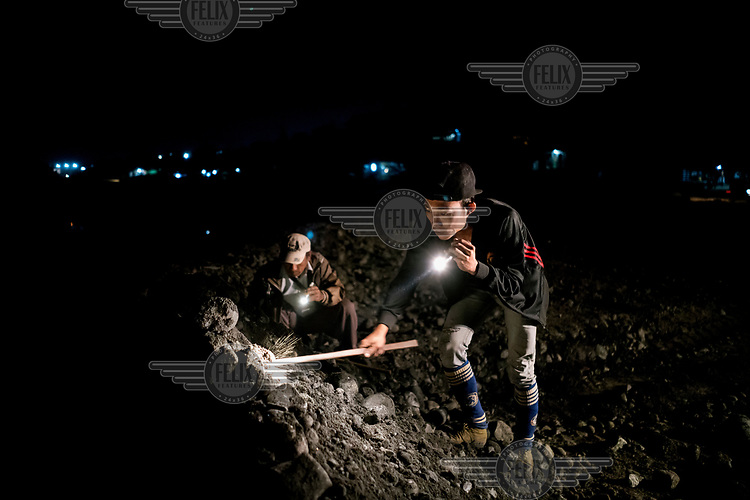 Freelance miners scavenge for jade rocks using torchlight as the discarded tailings from Hmaw Si Sar Mine are dumped from trucks.