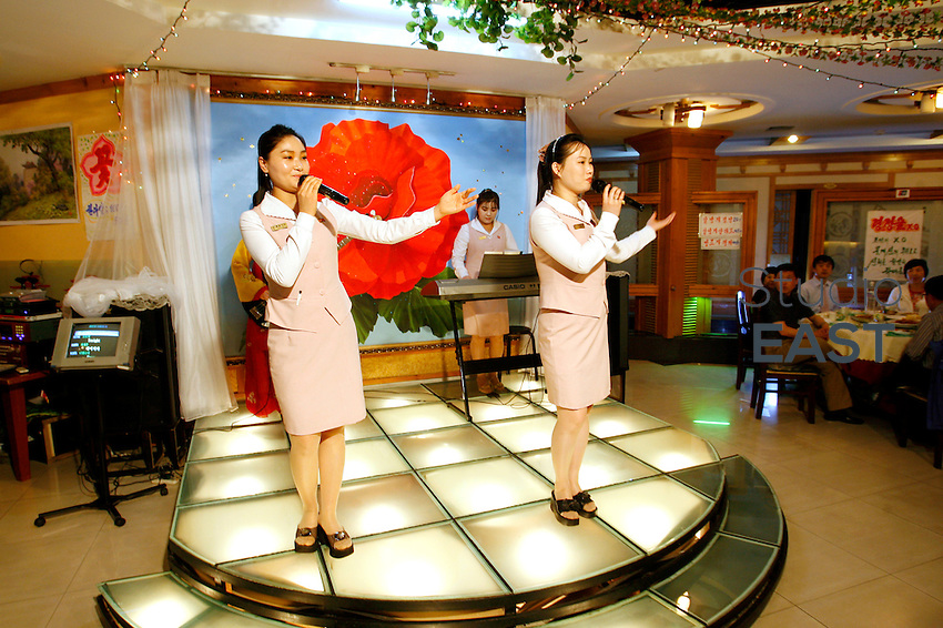 North Korean waitresses sing and entertain the audience at a North Korean restaurant, in Tonghua, Jilin province, China, on May 8, 2009. This restaurant is unique: it is the only North Korean restaurant with North Korean staff in China. The ten North Korean waitresses here are ones of the very few North Koreans, others than diplomats, allowed out of their country. All of them able to sing and dance, they come to China for an 3-year internship, missing very much their family left in North Korea. Photo by Lucas Schifres/Pictobank