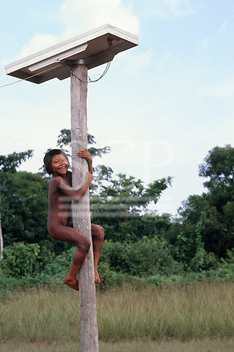 A-Ukre Village, Xingu, Brazil. Kayapo girl climbing pole which supports a solar panel power for medical post fridge.