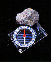 MAGNETITE (LODESTONE) WITH COMPASS<br /> The magnetic field of the ore deflects a compass needle from true north.