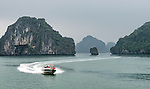 "A speedboat zooms across a section of Ha Long Bay. Ha Long Bay, located on the east coast of Vietnam near Haiphong, contains over 1,900 limestone ""karst"" islands projecting from the sea."