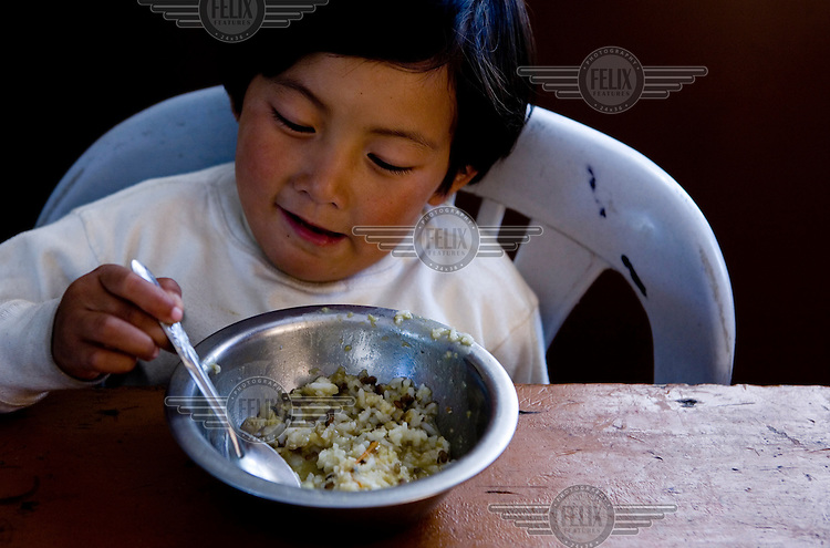 Young Tibetan orphan eats lunch at the Children's Village, which is working for the care and education of Tibetan refugee children in Dharamsala.