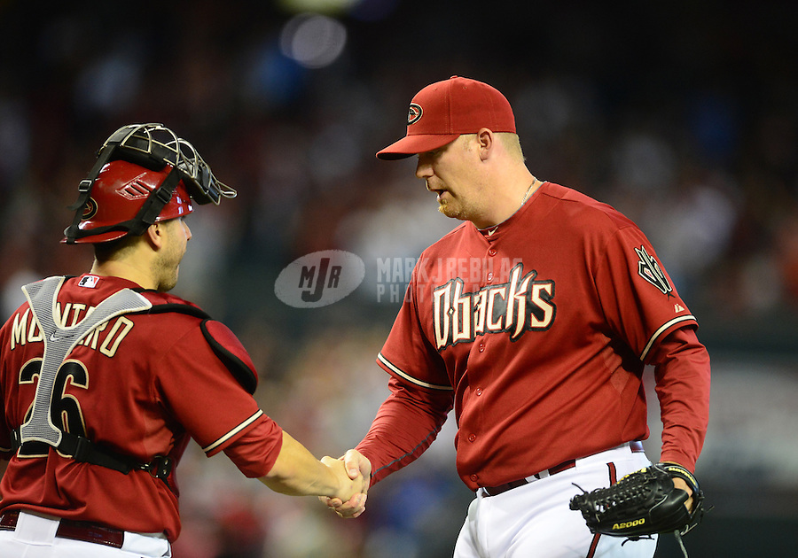 Apr. 22, 2012; Phoenix, AZ, USA; Arizona Diamondbacks pitcher J.J. Putz (right) celebrates with catcher Miguel Montero following the game against the Atlanta Braves at Chase Field. The Diamondbacks defeated the Braves 6-4. Mandatory Credit: Mark J. Rebilas-