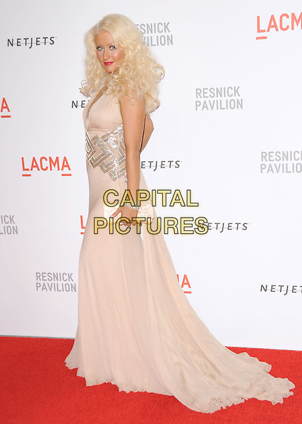 "CHRISTINA AGUILERA .at LACMA's ""The Unmasking"" The Lynda & Stewart Resnick Exhibition Pavilion Opening Gala at The Los Angeles County Museum of Art in Los Angeles, California, USA, September 25th 2010..full length long maxi dress gown train clutch bag beige nude halterneck silk chiffon silver tattoo bracelet     back over shoulder side rear behind                                                                 .CAP/RKE/DVS.©DVS/RockinExposures/Capital Pictures."