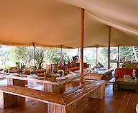 View over the rustic dining table towards the sitting area in the 'living' tent