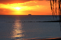 Ferry approaching los Cristianos harbour from the neighbouring island of La Gomera on a calm sea as the sun setts. Tenerife, Canary Islands.